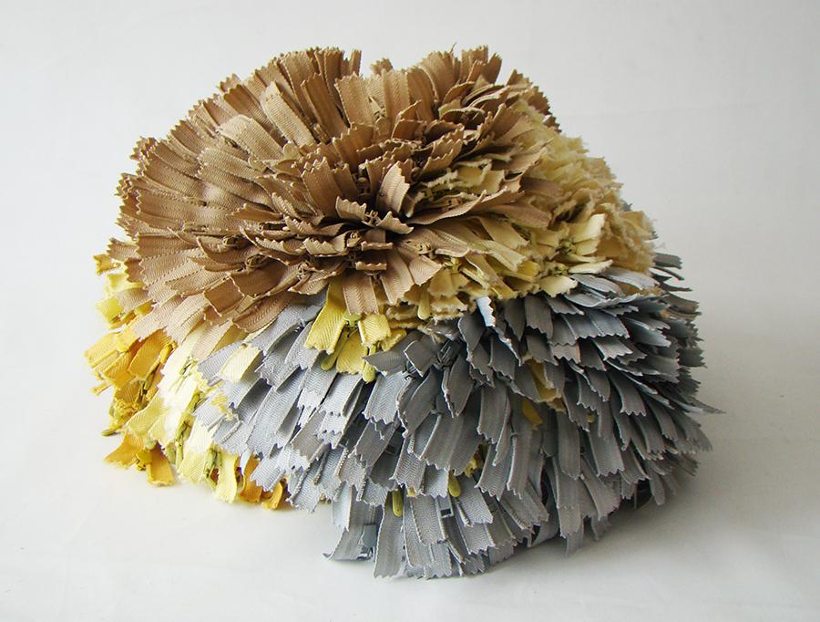 Cierres grises, amarillo claro y beiges amarrados en la base y que asemejan una flor de Hortensia